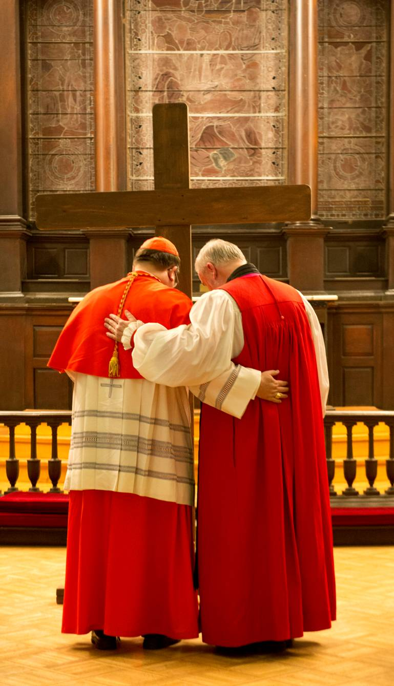 Cardinal Gerald Lacroix and Bishop Denis Drainville, the Roman Catholic and Anglican bishops of Quebec, share a quiet moment of prayer before the Cross on Good Friday, April 18, 2014